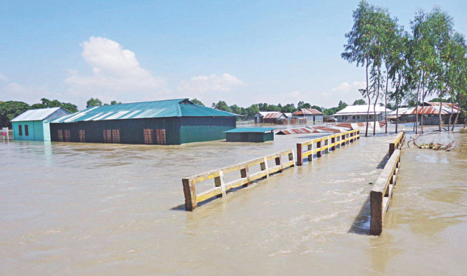 A bridge and a partially collapsed school under flood water in Islampur of Jamalpur yesterday. Several educational institutions of the district had to be closed due to the floods. Photo: Banglar Chokh