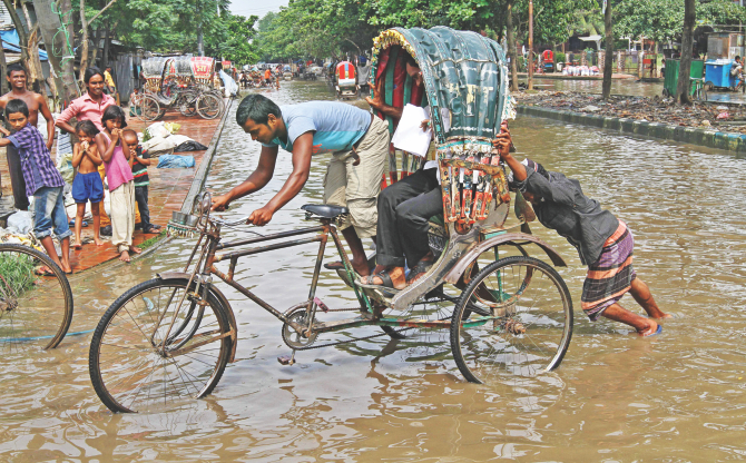 A passenger holds the handlebar while the rickshaw puller pushes the vehicle in ankle-deep water at Agargaon in the capital yesterday. The street has been under water for over a week and no government agency has done anything about it.  Photo: Amran Hossain