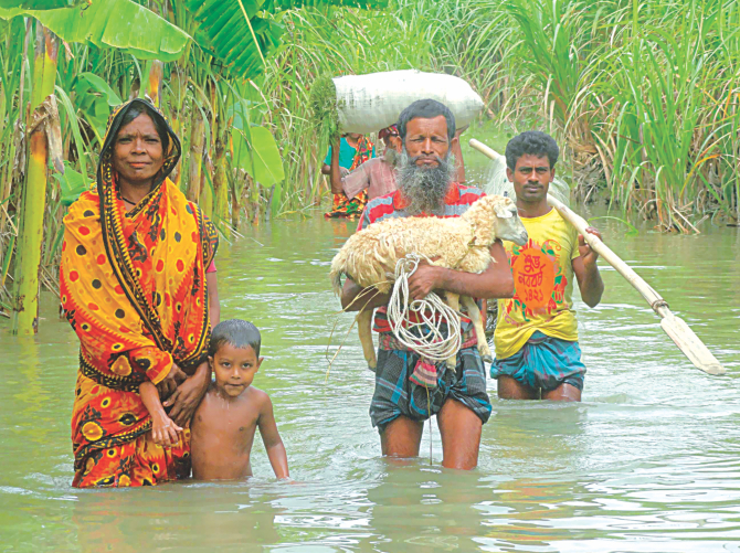 A family with their precious belongings moving to higher grounds wading through over knee-deep water at Char Shiberkuti in Lalmonirhat yesterday as flooding in the north continues to cause sufferings. Photo: Star
