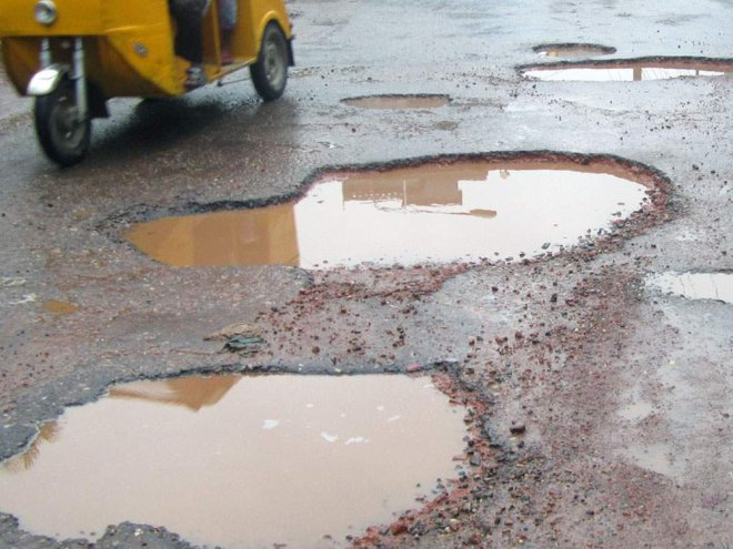Such potholes appearing in a large portion of Barisal-Dhaka highway in Barisal district during the ongoing monsoon make vehicular movement a tough job. The photo was taken from near Gournadi upazila headquarters in the district. PHOTO: STAR