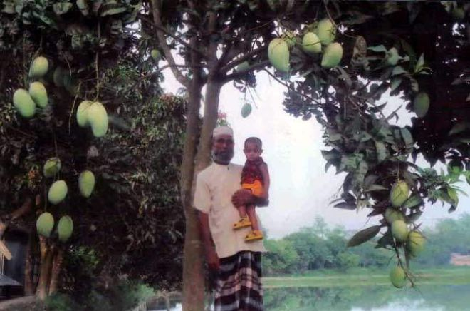Retired BGB man Moslemuddin, who successfully raised a mango orchard in Sadullapur upazila of Gaibandha, poses for photograph with his grandchild.  Photo: Star