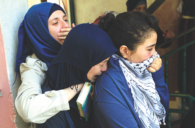 Relatives of killed Palestinian Mohammed al-Araj grieve during his funeral at the Qalandia Palestinian refugee camp near the West Bank city of Ramallah yesterday after he was shot and killed the night before during clashes with Israeli troops.  Photo: AFP