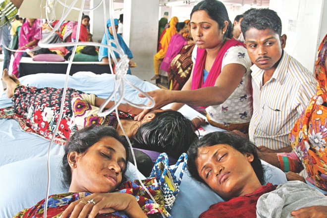 Hooked up to a saline drip, the garment workers of Tuba Group on their fourth day of hunger strike yesterday inside their factory in Badda of Dhaka. They have been demanding three months' arrears and Eid bonuses.  Photo: Amran Hossain