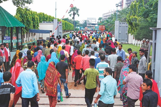 Garment workers of a factory in Ashulia report to duty as usual yesterday, defying a strike called by Tuba Group Sramik Sangram Committee, a temporary platform of 15 trade unions. Photo: Star