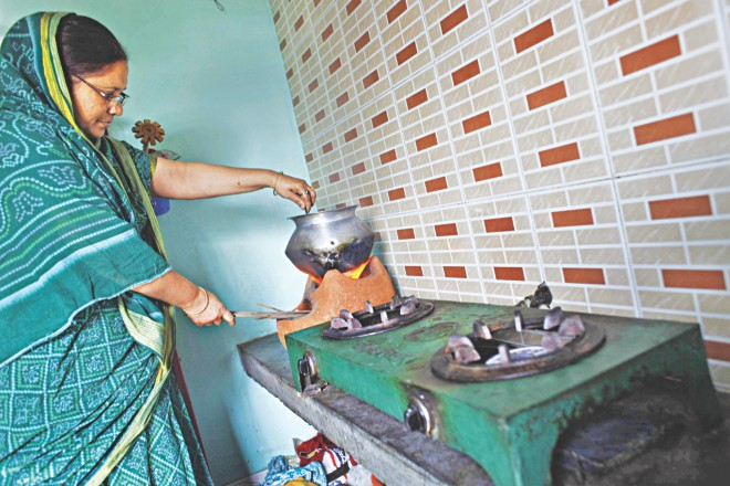 A homemaker cooks lunch on a wood-burning stove placed next to her gas-burning stoves in her kitchen in Mir Hazaribagh of Nobinagar in Demra in the capital. Titas blames the season for gas supply disruption, but many say that power plants and fertiliser factories leave too little gas for households. Photo: Rashed Shumon