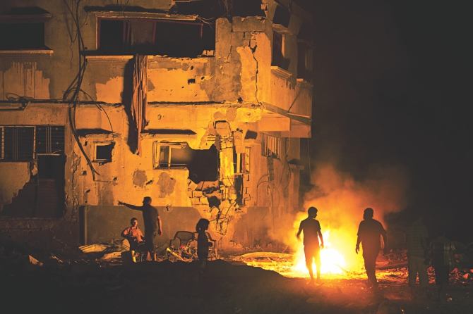 Members of two Palestinian families walk next to a fire amid destroyed homes on their block in Shejaiya on Wednesday. Shejaiya was one of the hardest hit neighborhoods in fighting between Hamas militants and Israel during the 50 days of fighting. The fire was set by the home owners in an effort to keep mosquitoes away from their shattered homes which have no water or electricity. Photo: AFP
