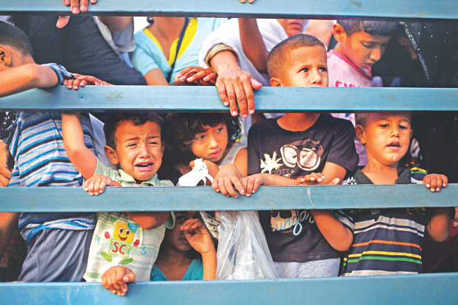 Palestinian children stand in the back of a truck as families leave their neighborhoods for safer locations amid continuing Israeli bombardment of Gaza yesterday.  Photo: AFP