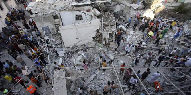 Rescue workers search for victims as Palestinians gather around the wreckage of a house, which witnesses said was destroyed in an Israeli air strike that killed at least nine members from the al-Ghol family, in Rafah in the southern Gaza Strip August 3, 2014. Photo: Reuters