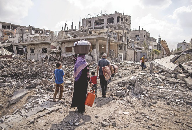 A displaced Palestinian family returns home amid the destruction in part of the northern Beit Hanun district of Gaza Strip after a 72-hour truce accepted by Israel and Hamas came into effect yesterday. The bloody 29-day-old Gaza conflict has killed 1,867 Palestinians and 67 Israelis.Photo: AFP, Independent.co.uk