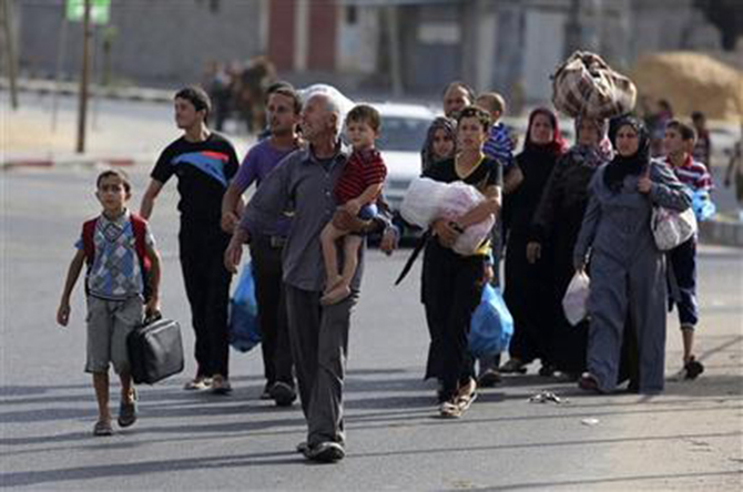 Palestinians flee their homes to take shelter at the United Nations school in Gaza City, Sunday. Photo: AP