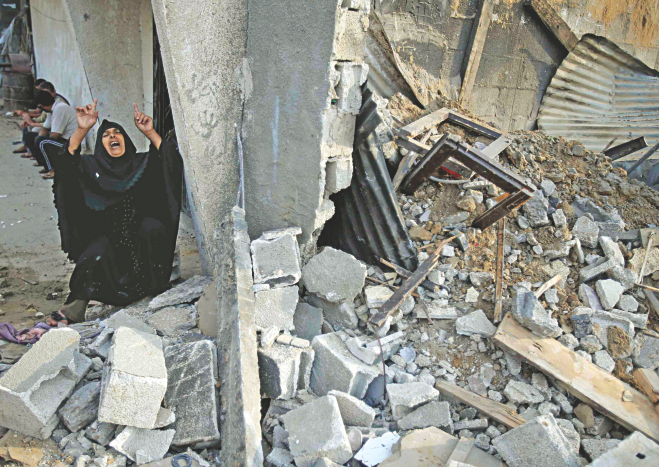 A Palestinian woman reacts next to the rubble of her relatives' house, which police said was destroyed in an Israeli air strike, in Khan Younis in the southern Gaza Strip yesterday. Israeli tanks shelled militant targets and a woman died in an air strike after the bloodiest day of a nearly two-week military offensive that showed no signs of abating, despite global calls for a truce. Photo: Reuters