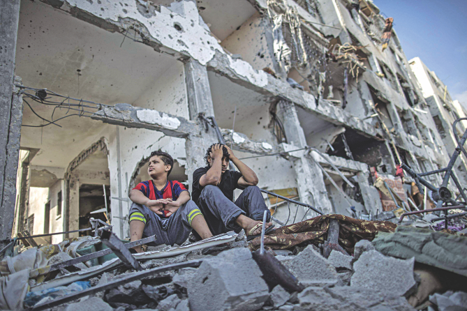 Palestinian brothers sit on the rubble of their house in front of an apartment block in part of the northern Beit Hanun district of the Gaza Strip after a 72-hour truce accepted by Israel and Hamas came into effect yesterday.     Photo: AFP