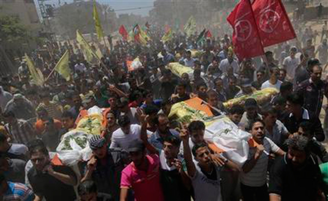 Palestinians carry bodies of seven people killed in a strike during their funeral in Khan Younis refugee camp in the southern Gaza Strip July 9. Photo: AP