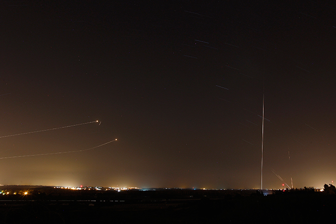 Rockets launched from the Gaza Strip towards Israel is seen (at right) as a rocket by the Iron Dome anti-missile system (at left) is fired to intercept them, before a five-day ceasefire was due to expire, August 19. Photo: Reuters