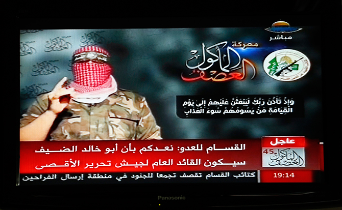Abu Ubaida, the spokesman of the Izz el-Deen al-Qassam Brigade, the armed wing of the Hamas movement, is pictured on a television screen as he delivers a televised statement on Hamas TV, in Gaza August 20. Photo: Reuters