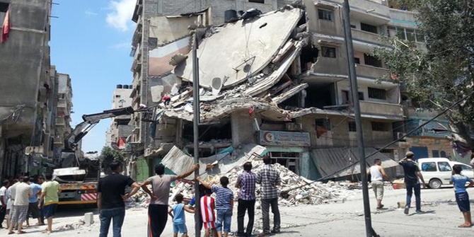 People in Gaza City look at a building destroyed by an Israeli air strike, 19 July. Photo: BBC