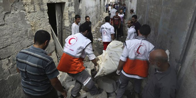 Palestinian medics carry a dead body found under the rubble of a home destroyed by an Israeli strike in the Shijaiyah neighbourhood of Gaza City, northern Gaza Strip, July 20. Photo: AP