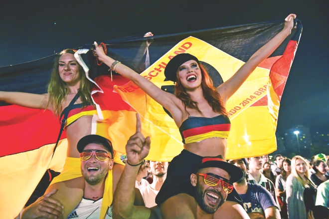 German fans enjoy their time as they watch the World Cup Round of 16 match between Germany and Algeria in Rio de Janeiro on Monday. PHOTO: AFP