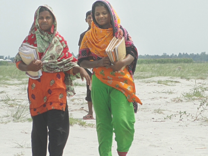 Two girls of Teesta Char village Narsingh of Aditmari upazila in Lalmonirhat go to high school for studying in the mainland every day, as their parents now understand the value of education. Photo: Star