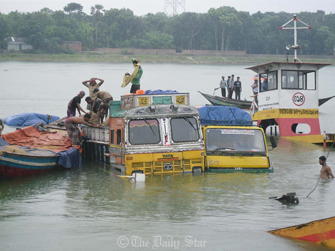 An over-loaded ferry carrying seven goods-laden trucks capsizes in Madhumati river near the pontoon of Kalna ferry ghat at Kashiani upazila of Gopalganj on Thursday.
