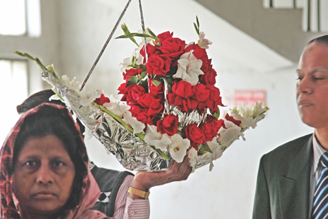 A man carries a flower bouquet shaped like a boat, the election symbol of ruling Awami League, to greet a minister at the secretariat yesterday.  Photo: Sk Enamul Haq