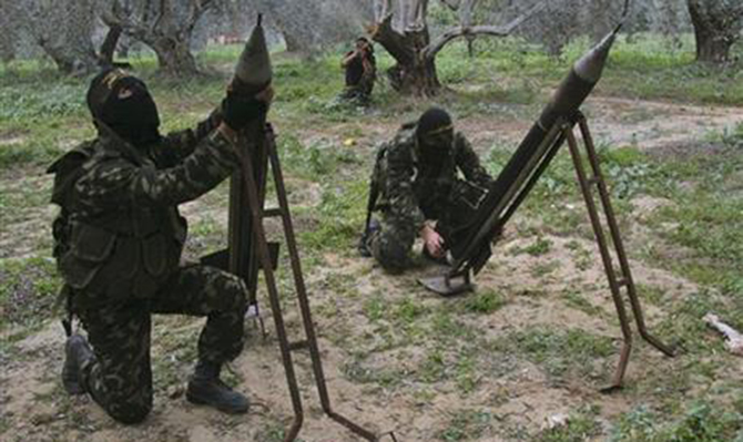 In this December 20, 2008, file photo, masked Palestinian militants from Islamic Jihad place homemade rockets before later firing them into Israel on the outskirts of Gaza City. Photo: AP