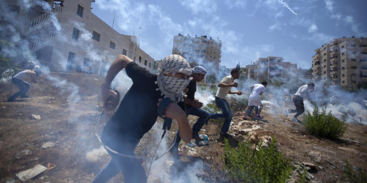 Palestinians run for cover during clashes with Israeli soldiers following a protest against the war in the Gaza Strip, outside Ofer, an Israeli military prison near the West Bank city of Ramallah Aug 1. Photo: AP