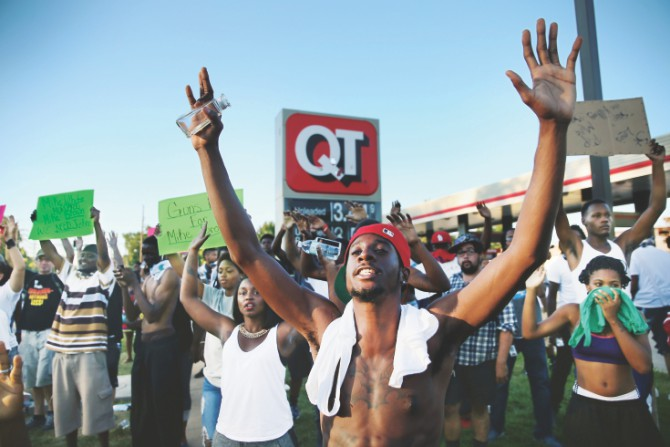 """Hands up, don't shoot"". Ferguson has turned the gesture into a defiant symbol. Photo: Vox.com"