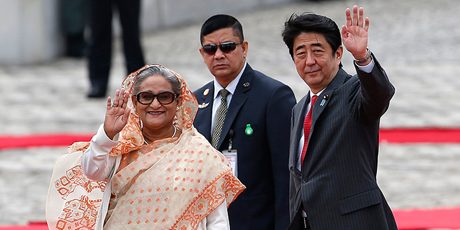 Prime Minister Sheikh Hasina (L) waves to children with Japan's Prime Minister Shinzo Abe (R) during a welcome ceremony at the state guest house in Tokyo on Monday. Photo: Reuters