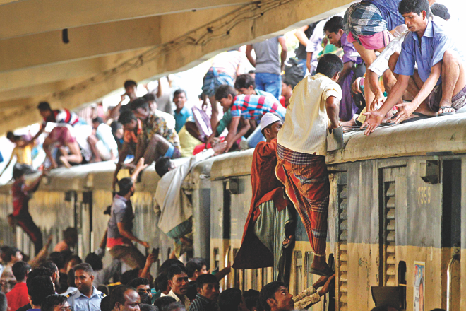 People heading home for the holidays scramble on to the roof of a train, failing to find space to stand inside the carriages at Kamalapur Railway Station yesterday. The railway sells a large number of standing tickets especially during the Eid holidays to cope with huge rush. Photo: Palash Khan