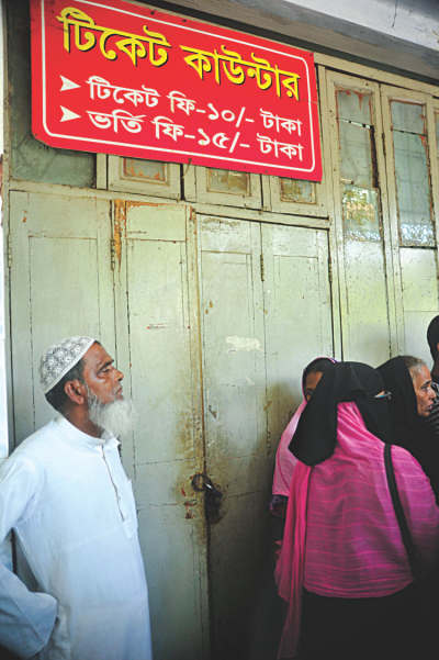 Patients and their attendants, right, wait for the ticket counter to open at the outdoor section. Photo: Firoz Ahmed