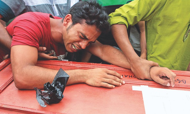 Shah Poran breaks down in tears holding the coffin of his brother Selim at Hazrat Shahjalal International Airport in the capital where his body arrived along with five other corpses yesterday. Nine Bangladeshi workers were killed in a factory fire in Saudi Arabia on May 12. Six bodies were flown home on a Biman Bangladesh flight yesterday. Photo: Star