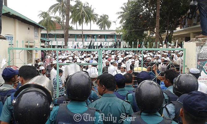 "Law enforcers intercept Hefajat men at the gate of Nuria Madrasa in Kamrangairchar in the capital tried to bring out a procession under the banner of Bangladesh Khelafat Andolon protesting what they termed ""government action"" on their rally on May 5 last year. Photo: Prabir Barua Chowdhury/ Star"