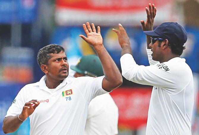Sri Lanka spinner Rangana Herath (L) celebrates taking yet another Pakistan wicket with captain Angelo Mathews during the third day's play of the second Test in Colombo on Saturday. PHOTO: REUTERS