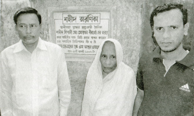 Bir Sreshtho Muhammad Mustafa's mother, brother (L) and nephew in front of the memorial plaque.