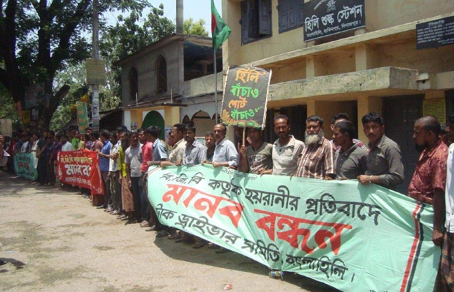 Port users of Hili Land Port form a human chain in front of the customs office at Hakimpur in Dinajpur yesterday to press their three-point demand. Photo: Star