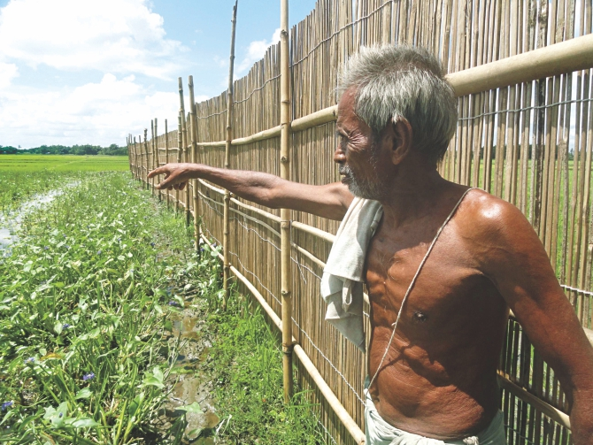 A Hindu farmer points to his land, which is being used illegally by some BNP men for fish farming in Dulali Beel of Lalmonirhat's Aditmari upazila. Photo: Star