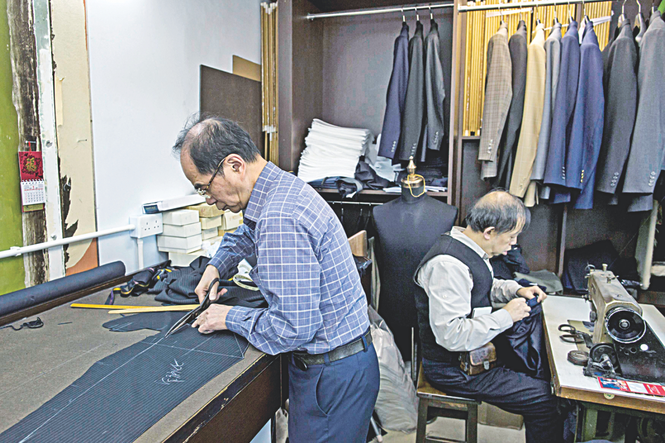 Tailors work at a workshop at Hong Kongs Tsim Sha Tsui shopping district. Photo: Reuters
