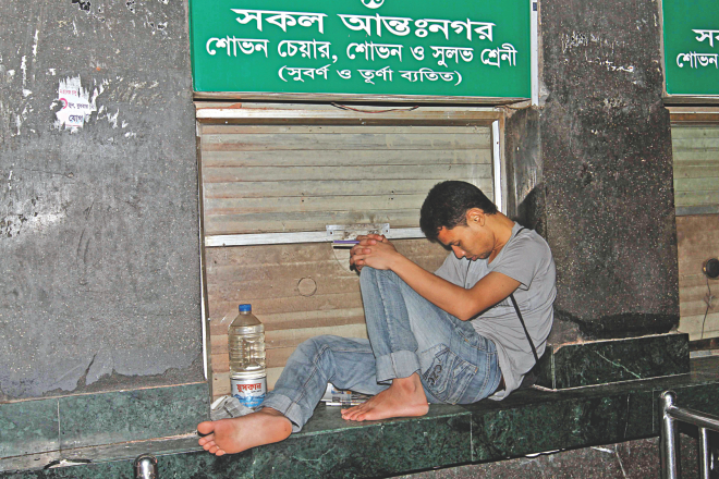 In an awkward position, a man sleeps on a ticket counter at Kamalapur Railway Station in the wee hours of yesterday to keep his first place in line for advance tickets for Eid. He had been waiting there since 5:00pm Saturday. He got the tickets around 9:00am yesterday. Photo: Anisur Rahman