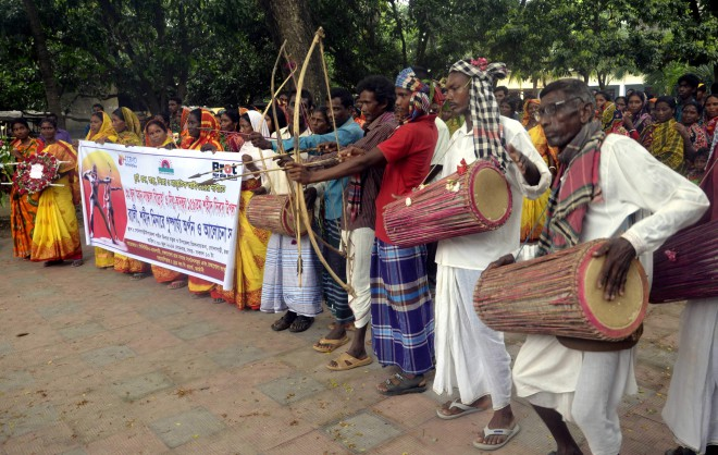 Indigenous people belonging to Santal community perform archery during their traditional cultural programme in Godagari upazila headquarters under Rajshahi district yesterday, marking 159th anniversary of the Santal Hul, an anti-British uprising by the community.   PHOTO: STAR