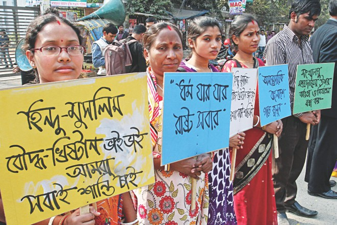 "Social Improvement Society forms a human chain in front of Jatiya Press Club in the capital yesterday protesting the barbaric attacks on Hindus across the country. A participant holds a placard saying, ""Hindus-Muslims-Buddhists-Christians are brothers, we all want peace."" Photo: Star"