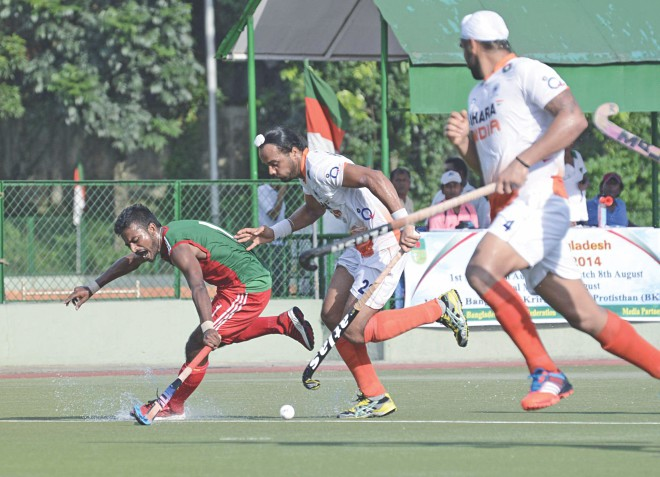 A Bangladesh player (L) attempts to thwart an Indian attack during their second match of the three-match series at the Bangladesh Krira Shikkha Protishthan turf yesterday. The hosts lost the match 1-5. PHOTO: STAR
