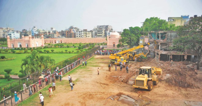 Two bulldozers and a crane knocking down a building illegally built on the northwest part of Lalbagh Fort in the capital yesterday. The Department of Archaeology finally succeeded in getting one of the illegal buildings demolished through its relentless efforts since 2009.   Photo: Star