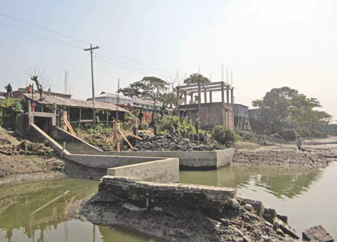 A section of local influential people continue to occupy land and erect permanent structures around a sluice gate at Bablatala Bazar in Kalapara upazila of Patuakhali, much to the worry of the farmers there. PHOTO: STAR