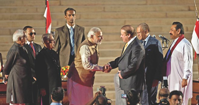Narendra Modi, after his swearing-in ceremony at the Presidential Palace in New Delhi yesterday, shakes hands with his Pakistani counterpart Nawaz Sharif as Sri Lankan President Mahinda Rajapaksa looks on.   Photo: AFP