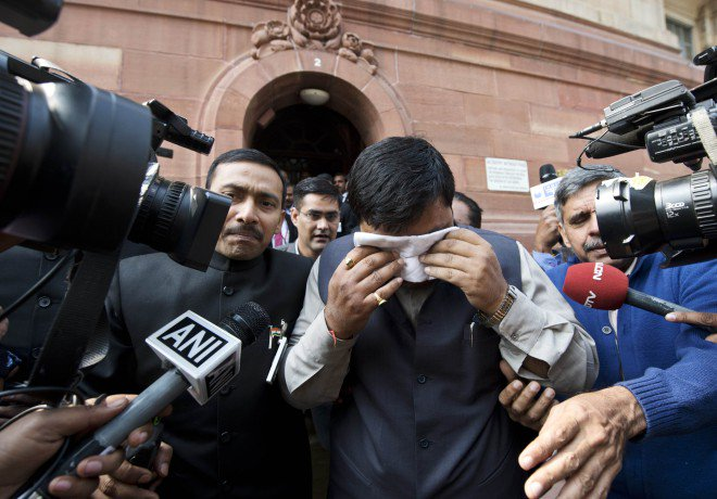 An unidentified member of India's Parliament, holding a handkerchief to his face after being affected by pepper spray, leaves parliament after protests inside the building in New Delhi, yesterday. Photo: AFP