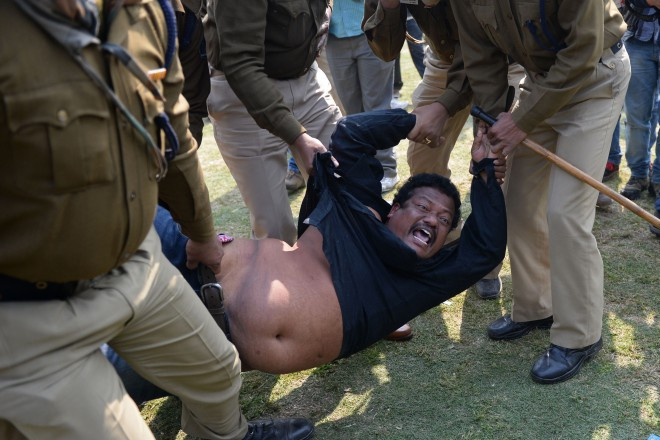 A demonstrator demanding a separate state of Telangana is detained by policemen outside the parliament building. Photo: AFP