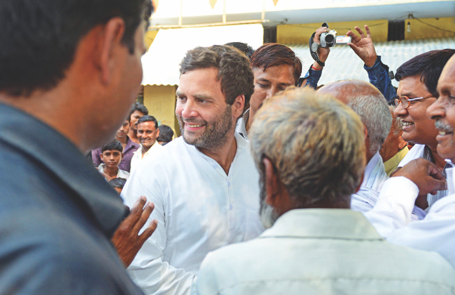 Indian Congress Party Vice President Rahul Gandhi (2L) speaks with residents near a polling station during voting in Amethi yesterday. Photo: AFP