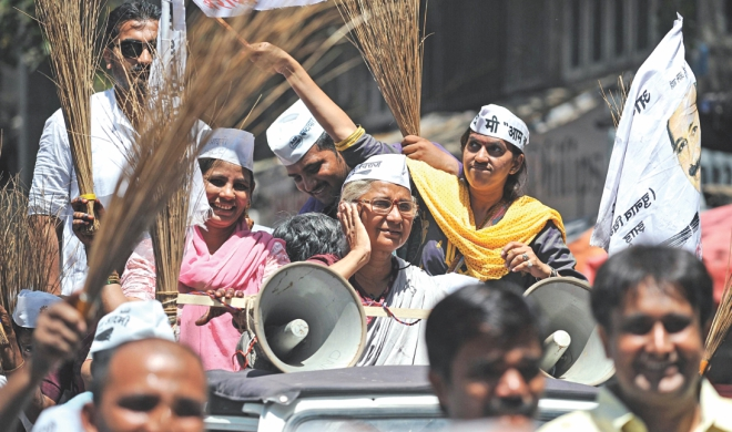 Supporters of AAP candidate Medha Patkar (C, on jeep) wave brooms - her party symbol - during a rally in Mumbai, yesterday.