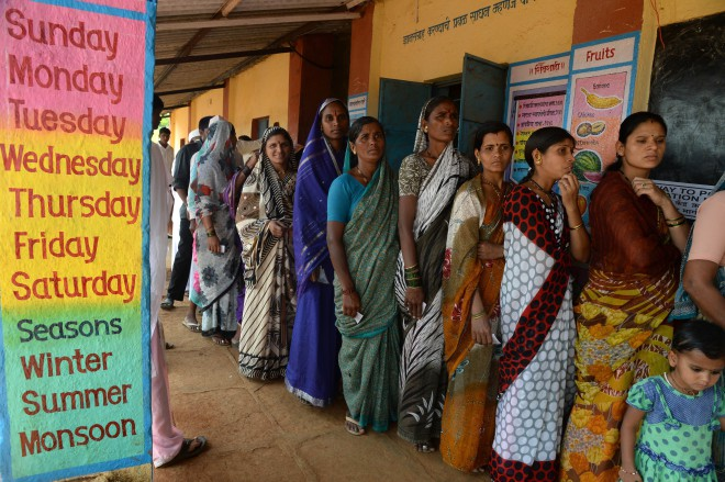 Indian women wait to cast their vote at a polling booth inside a primary school in Shirgaon village of Pune district, some 130 kms south-east of Mumbai yesterday. India hosted its biggest day of voting with the ruling Congress party battling to stem a further slide in the polls against the opposition Hindu nationalists after another week of damaging headlines. Photo: AFP